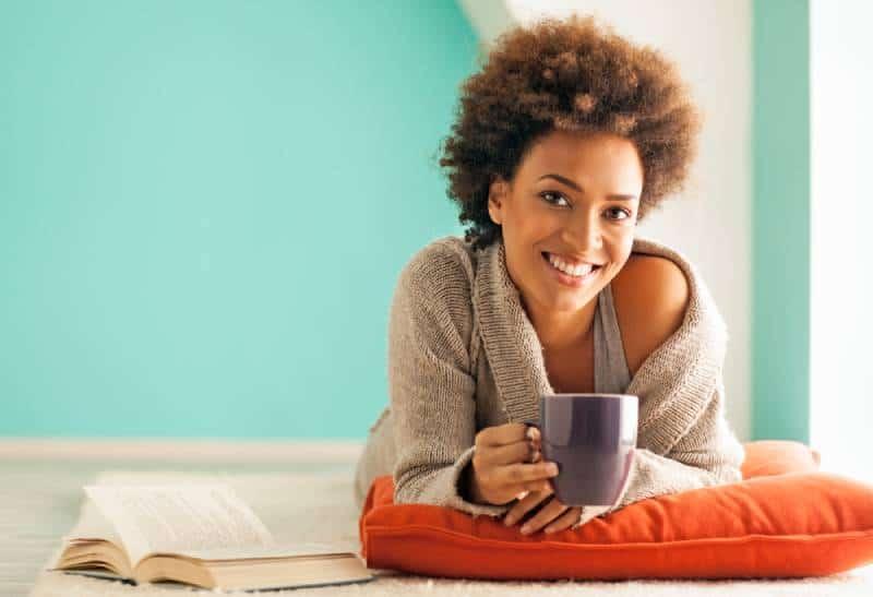 junge Frau, die eine Tasse Kaffee genießt, während sie zu Hause entspannt
