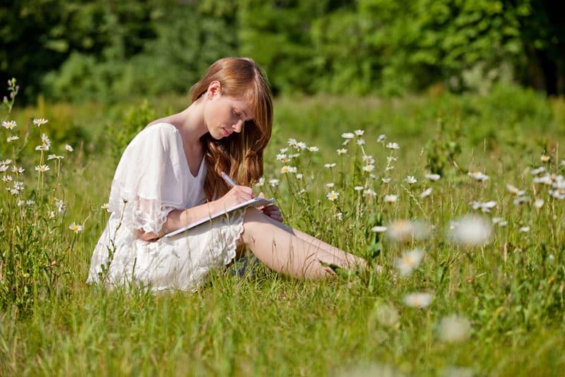 junge Frau, die einen Brief in der Wiese schreibt