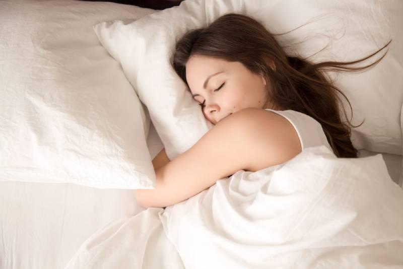 junge Frau, die gut im Bett schläft und weiches weißes Kissen umarmt