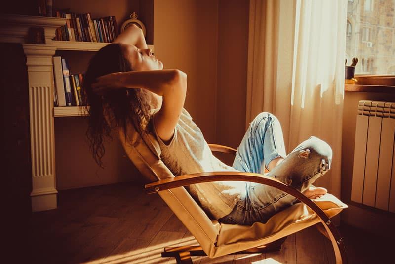 junge Frau, die sich auf dem Stuhl entspannt