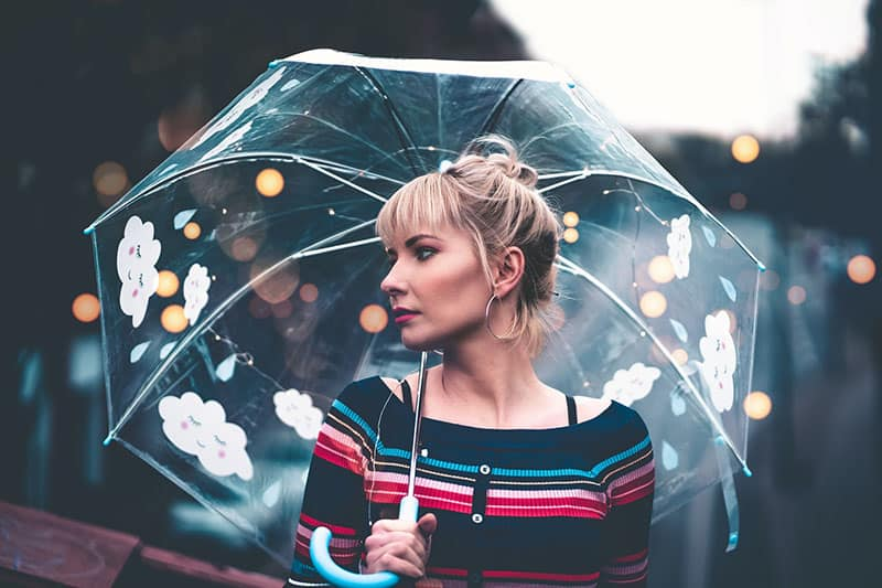 junge Frau hält einen Regenschirm