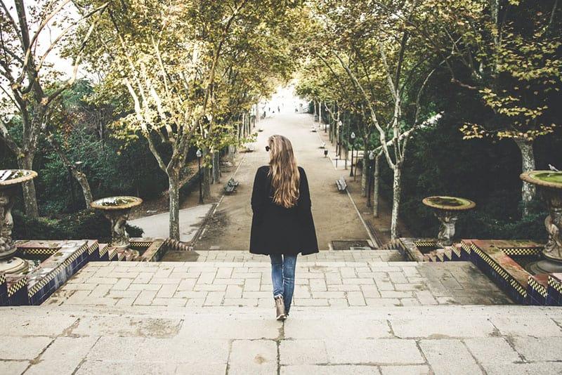 junge Frau im schwarzen Mantel zu Fuß