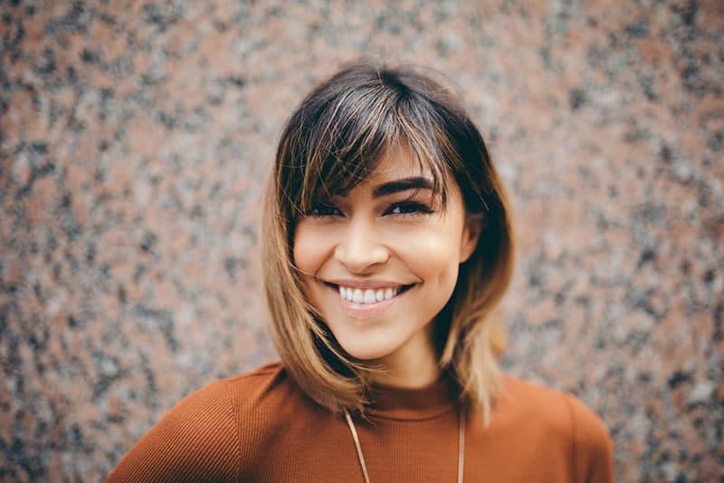 junge Frau mit kurzen Haaren lächelnd