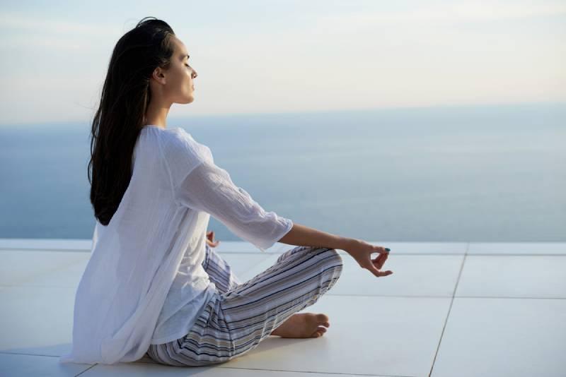 junge Frauen üben Yoga-Meditation auf Sonnenuntergang mit Meerblick im Hintergrund