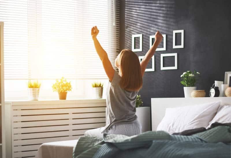 junge glückliche Frau wachte am Morgen im Schlafzimmer am Fenster mit dem Rücken auf