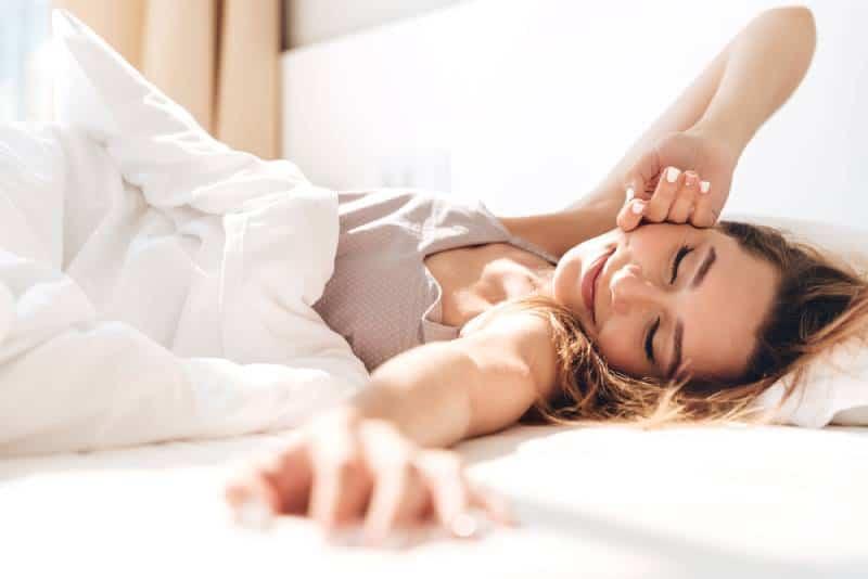junge lächelnde hübsche Dame liegt im Bett drinnen.