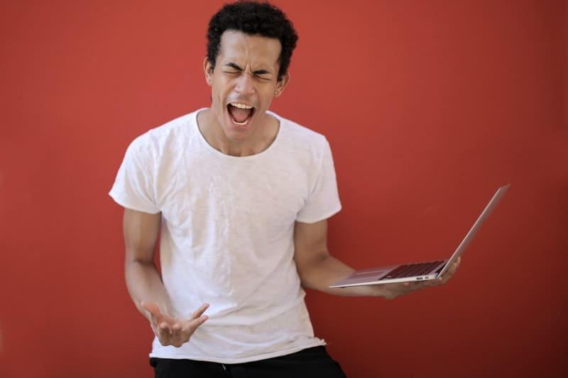 junger Mann, der über Laptop brüllt