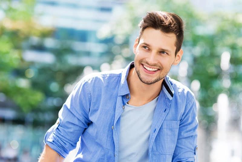 junger Mann im blauen Hemd lächelnd
