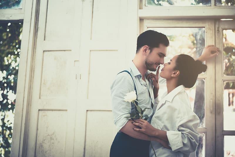 junger Mann küsst seine Frau vor der alten Tür