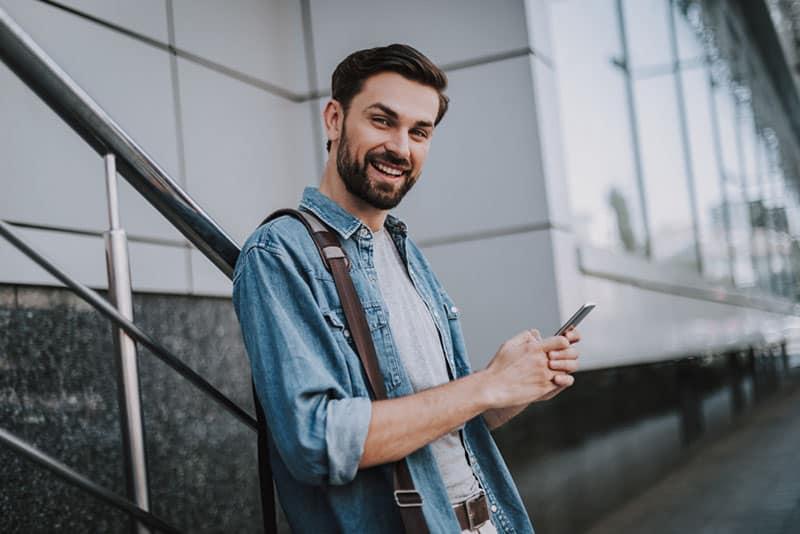 junger Mann lächelt und hält ein Telefon