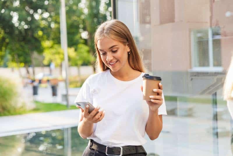 junges Mädchen, das draußen auf ihrem Telefon tippt
