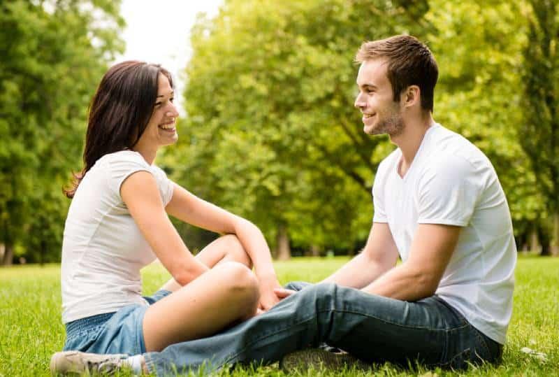 junges Paar, das auf Gras in der Natur sitzt