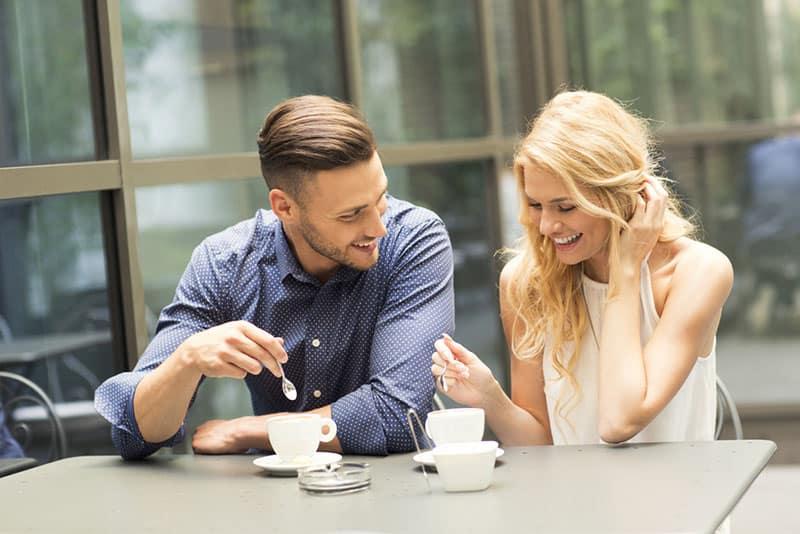 junges Paar lächelt und trinkt Kaffee