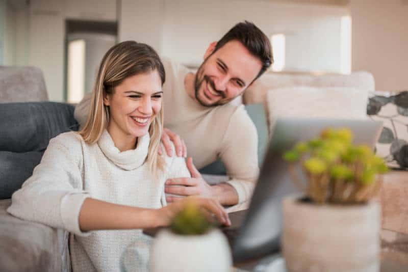 junges glückliches Paar, das im Wohnzimmer sitzt und auf Laptop tippt