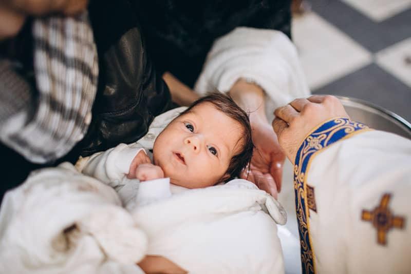 kleines Baby bereit für die Taufe in der Kirche