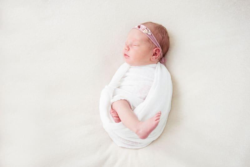 kleines Baby in Weiß gewickelt