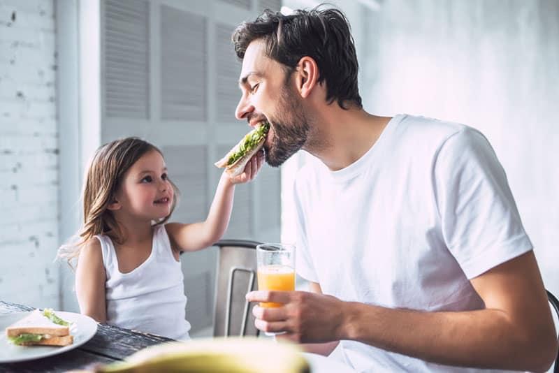 kleines Mädchen, das ihrem Vater ein Sandwich gibt