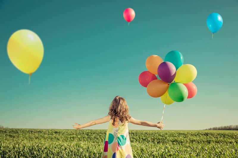 kleines Mädchen, das mit bunten Luftballons spielt