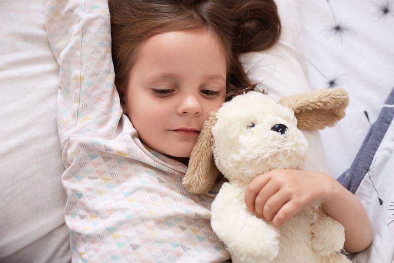 kleines Mädchen hält ihr Spielzeug