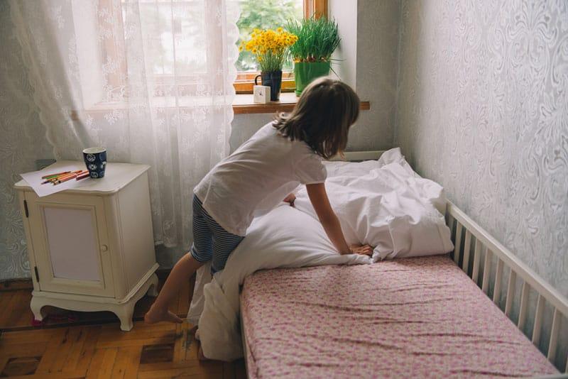 kleines Mädchen putzt ihr Zimmer