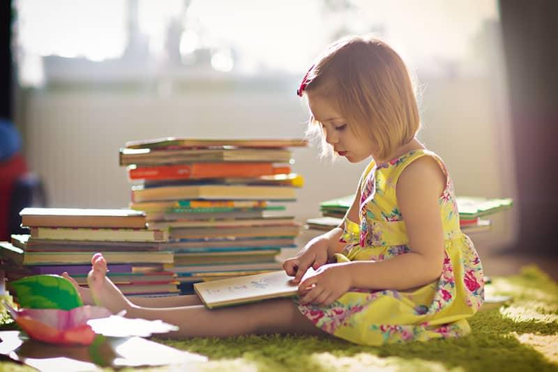 kleines Mädchen spielt mit Büchern