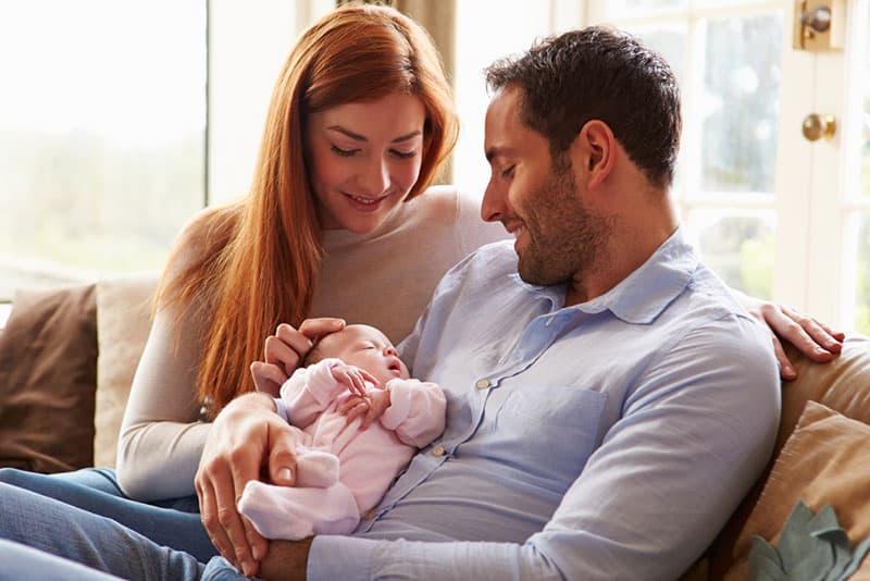 lächelnde Eltern halten ihr Baby