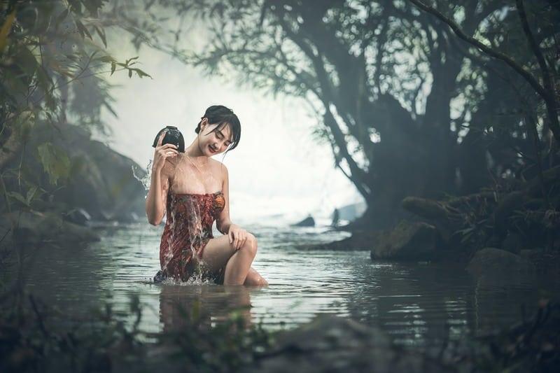 lächelnde Frau badet im See