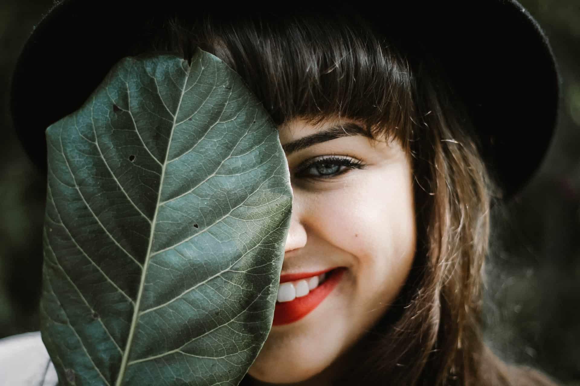 lächelnde Frau, die Blatt hält