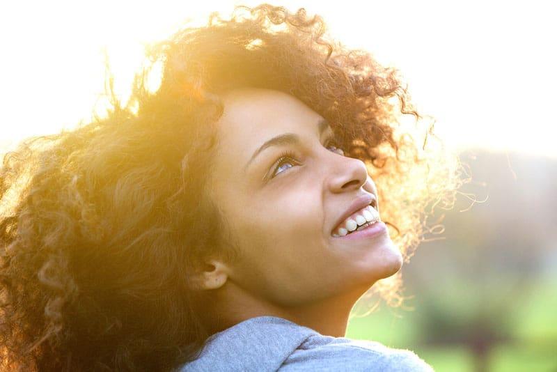 lächelnde Frau, die Himmel betrachtet