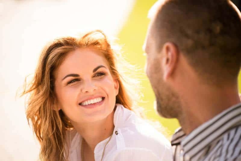 lächelnde Frau, die Mann während des Tages betrachtet