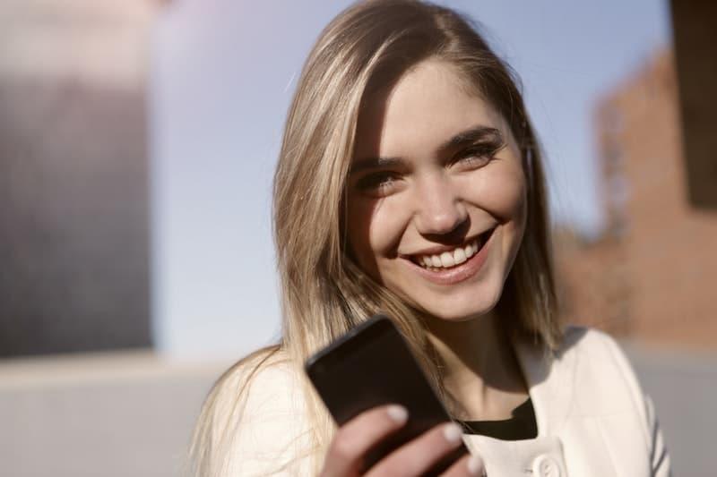 lächelnde Frau, die Telefon hält