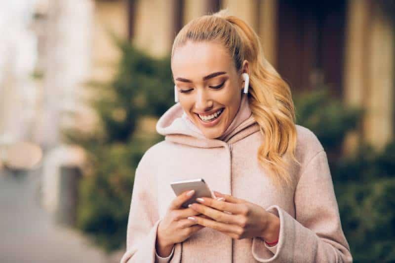 lächelnde Frau, die auf ihrem Telefon tippt und draußen Musik hört