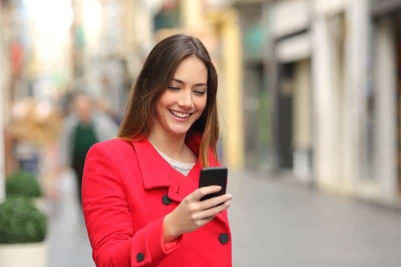 lächelnde Frau, die ihr Telefon auf der Straße betrachtet