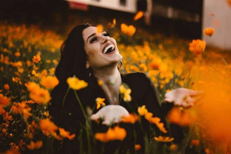lächelnde Frau, die im Blumenfeld sitzt