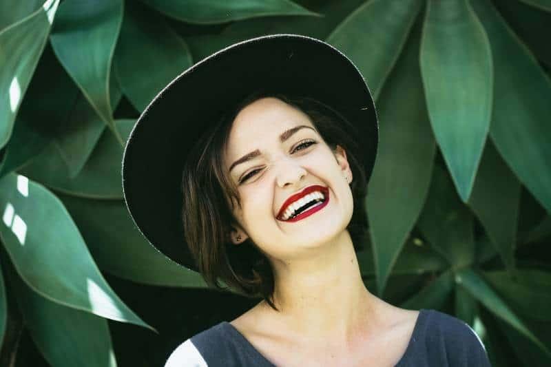 lächelnde Frau, die neben Pflanze steht
