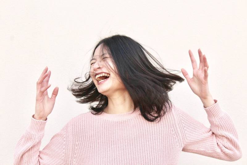 lächelnde Frau, die rosa Pullover trägt