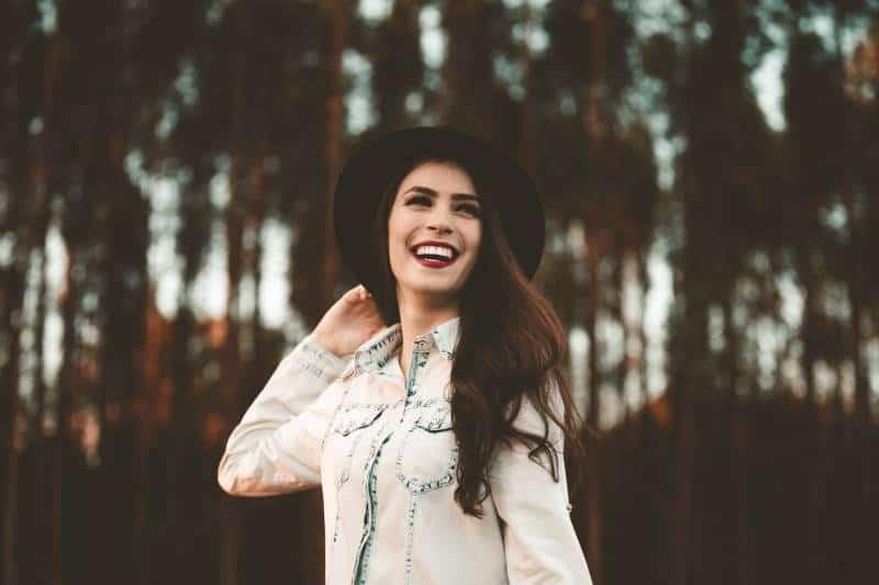 lächelnde Frau, die schwarzen Hut trägt und im Wald steht