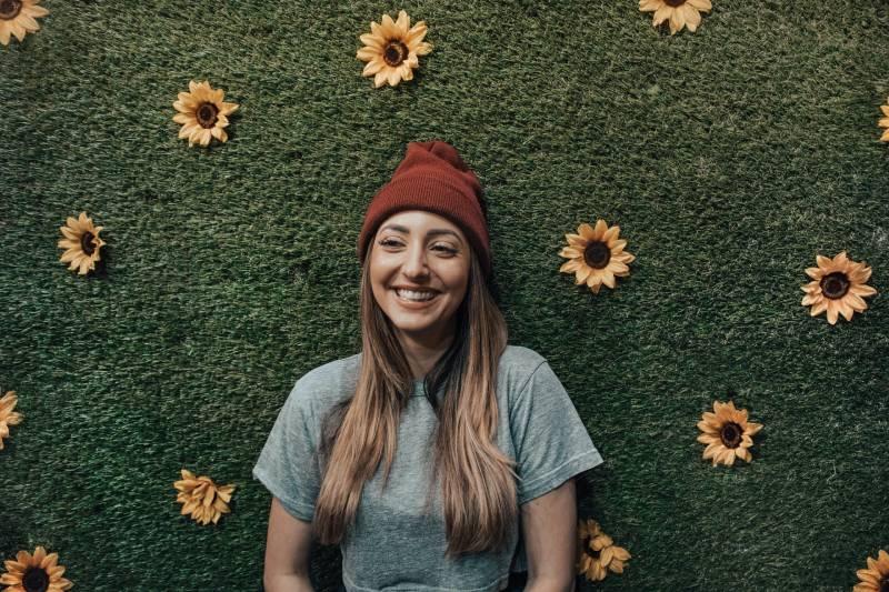 lächelnde Frau, die sich auf Blumenwand stützt