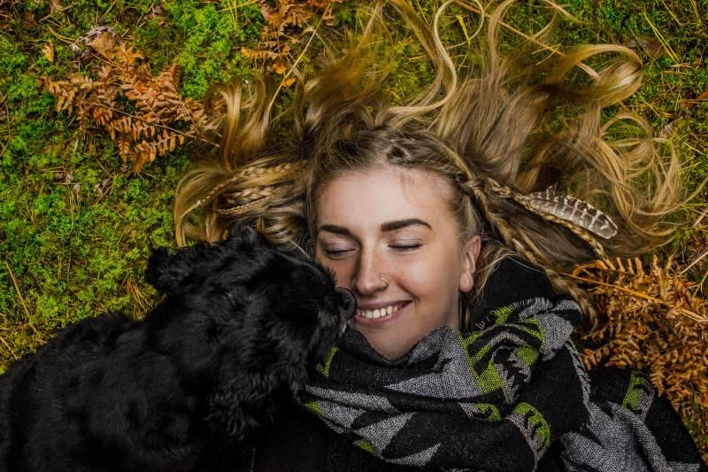lächelnde Frau, die tagsüber neben schwarzem Hund auf dem Boden liegt