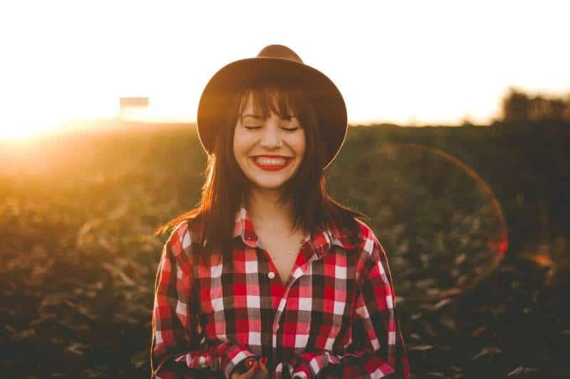 lächelnde Frau im weißen und roten karierten Kleid