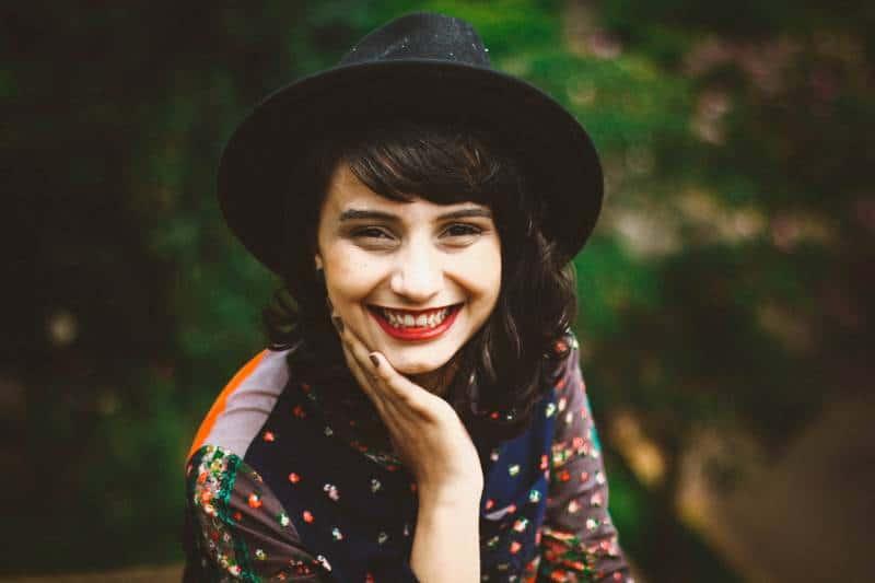 lächelnde Frau mit Hut draußen