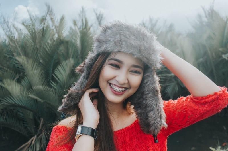 lächelnde Frau mit Uhr und Mütze