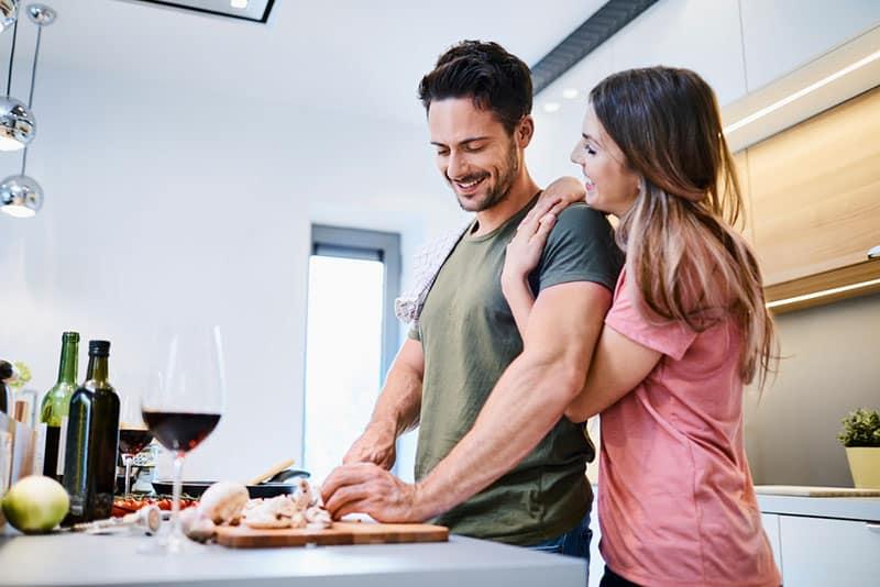 lächelnde Männer, die für seine Frau kochen