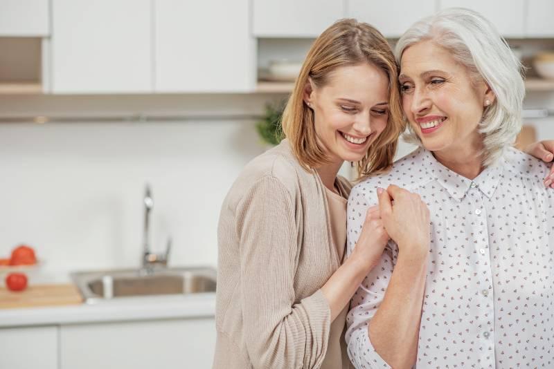 lächelnde Mutter und Tochter, die in der Küche stehen