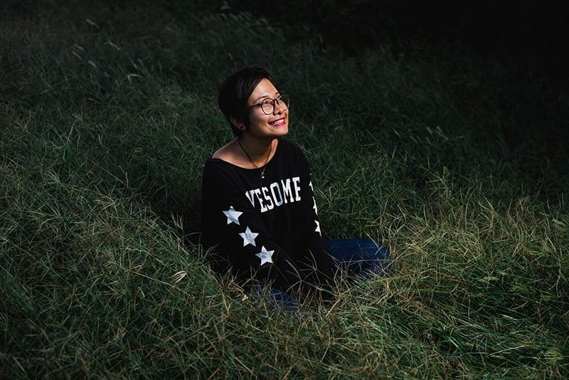 lächelnde asiatische Frau, die auf dem Gras sitzt