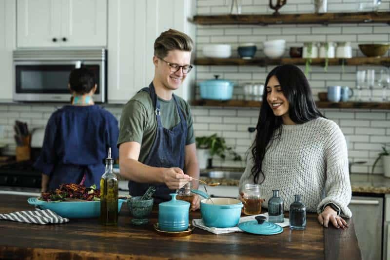 lächelnder Mann stehend und mischend nahe Frau im Küchenbereich des Hauses