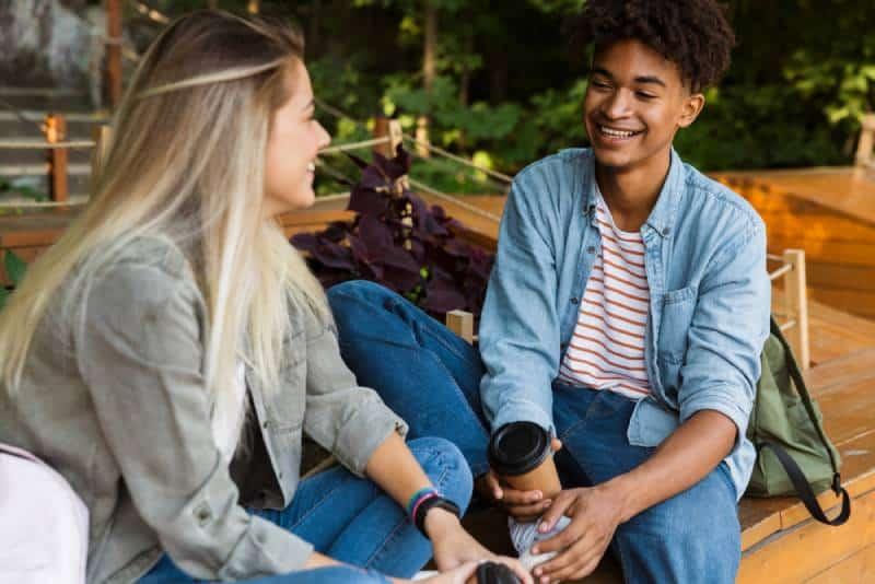 lächelnder Mann und Frau sprechen im Café