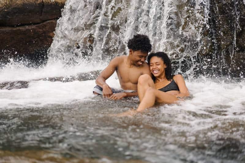 lächelnder topless Mann, der nahe seiner Freundin nahe Wasserfall sitzt