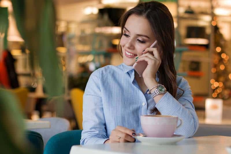 lächelndes Mädchen, das an ihrem Telefon im Café spricht