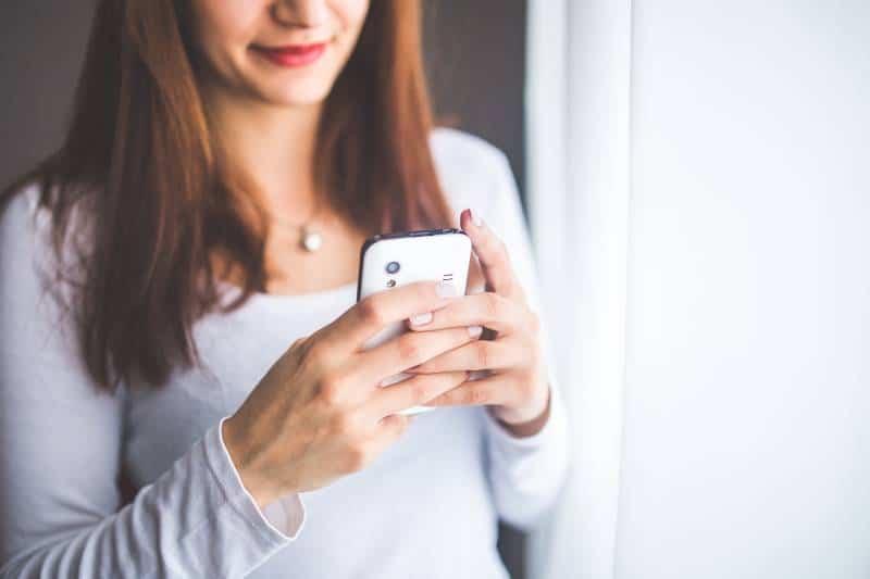 lächelndes Mädchen, das zu Hause SMS schreibt